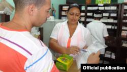 Una farmacéutica muestra una circular del MINSAP que avala la calidad de los condones Momentos.