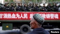Un hombre uigur observa un camión que transporta policías paramilitares durante un mitin de juramento antiterrorista en Urumqi, Región Autónoma Uigur de Xinjiang, en 2014 (Archivo).