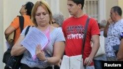 Una cubana revisa sus papeles tras visitar una oficina de inmigración en La Habana, Cuba.