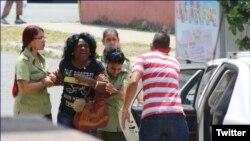 Agentes de la policía política arrestan a Berta Soler este jueves, cuando salía de la sede de las Damas de Blanco, en Lawton, La Habana. (Foto: Angel Moya)