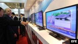 Varias personas observan una emisión de televisión digital en el stand de una compañía china que participa en la XV Convención y Feria Internacional Informática 2013.