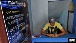 Un cuentapropista técnico en reparación de celulares espera llegada de clientes a su local.