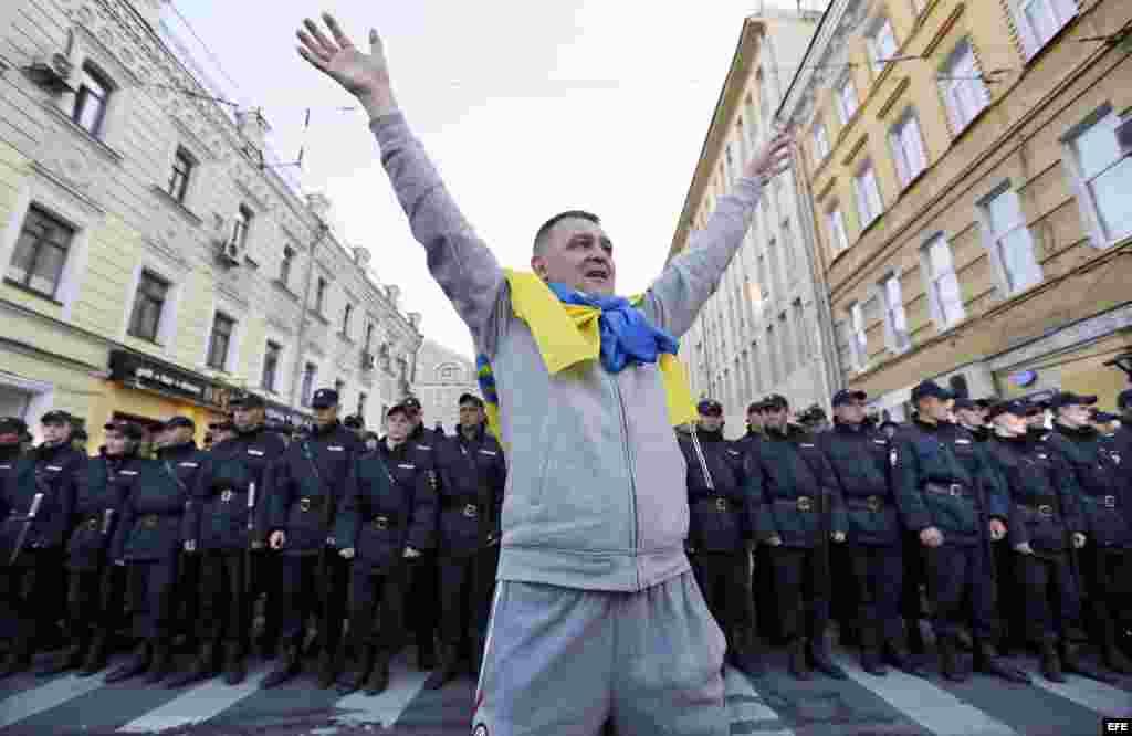 Frente a la policía de Moscú con la bandera de ucrania al cuello.