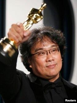 """Bong Joon Ho sostiene en alto la estatuilla del Oscar por """"Parasite"""". REUTERS/Danny Moloshok"""