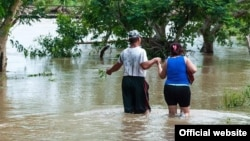 Una pareja se desplaza con el agua a la rodilla en una zona inundada en Cuba por la tormenta Alberto. (Vanguardia)
