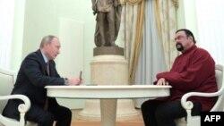 Vladimir Putin (i) con el pasaporte de Rusia para Steven Seagal