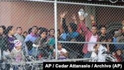 En esta foto del 27 de marzo de 2019, migrantes centroamericanos esperan comida en una estructura erigida por la Oficina de Control de Aduanas y Fronteras de EE. UU. para procesar la oleada de familias migrantes y menores no acompañados en El Paso, Texas. Foto: AP / Cedar Attanas