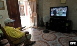 Un hombre ve desde su casa la transmisión en vivo la sesión de la Asamblea Nacional.