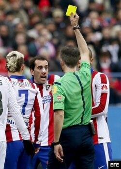 El árbitro Fernández Borbalán muestra tarjeta amarilla al defensa uruguayo del Atlético de Madrid, Diego Godín.
