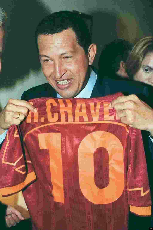 El presidente de Venezuela, Hugo Chávez, muestra una camiseta de béisbol con su nombre, que le entregó un compatriota a su llegada a la sede de la CEOE en octubre de 1999, donde asistió a una reunión con empresarios españoles y venezolanos.