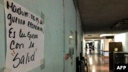 """Un cartel en una pared del Hospital Universitario, en Caracas, reza: Maduro, no es la guerra económica, es tu guerra contra la salud""""."""