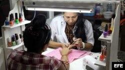 Una manicurista atendiendo a una clienta en un local rentado al estado