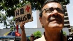 Una mujer sostiene un cartel durante protesta contra régimen de Nicolás Maduro en Caracas (Foto AP)