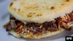 Arepa rellena de carne y tocineta, alimento típico venezolano en Caracas (Venezuela).