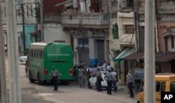 Sospechosos de coronavirus son evacuados en un bus del MINSAP y escoltados por la policía cerca del Mercado de Cuatro Caminos, en La Habana. (AP/Ismael Francisco)