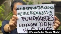Una mujer con un cartel exige la liberación de los 3 miembros de la ONG FundaRedes