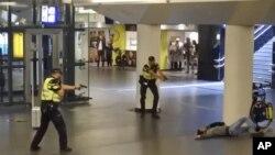 Dos policías holandeses apuntan sus armas hacia un hombre abatido a disparos por los agentes después de que éste apuñaló a dos personas en la estación central de trenes en Amsterdam.