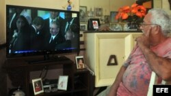 Un hombre observa en televisión el momento en el que el mandatario estadounidense, Barack Obama, estrecha la mano de Raúl Castro.