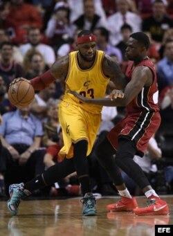 LeBron James (i) de los Cleveland Cavaliers en acción ante Luol Deng (d) de los Miami Heat.