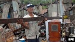 """Un hombre rescata algunas pertenencias de su hogar, destruido por el paso del huracán """"Sandy"""", en la ciudad de Santiago de Cuba. La urbe, en el este de la isla, fue una de las zonas más castigadas por el paso del huracán, con derrumbes de viviendas"""