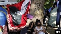 Dos activistas sentadas bajo un árbol observan un teléfono móvil, junto a una bandera del fundador de la República, Mustafa Kemal Ataturk, en el parque Gezi de Estambul, Turquía