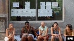 Un grupo de vecinos conversa junto a una vidriera donde se exponen las biografías de los candidatos.