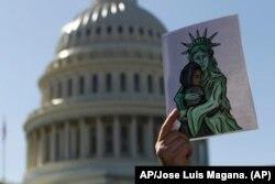Un activista muestra una imagen a favor de los refugiados durante una manifestación frente al Capitolio de los EE. UU. En Washington, el 15 de octubre de 2019. Foto: AP /Jose Luis Magana.
