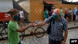 El saludo de dos cubanos en una calle de La Habana en vísperas del Día de los Pades (Yamil Lage/AFP).