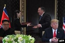 Kim Yo Jong y Michael Pompeo intercambian documentos en la ceremonia de firma de acuerdos de la histórica cumbre de Singapur entre Kim Jong Un y el presidente Donald Trump, el 12 de junio de 2018. (SAUL LOEB / AFP)