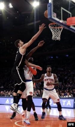 Brook López (i), de los Nets de Brooklyn, intenta anotar ante Iman Shumpertlos y Amar'e Stoudemire (c), de los Knicks de Nueva York.
