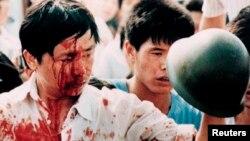 Un manifestante herido sostiene el casco de un militar en la Plaza de Tiananmen el 4 de junio de 1989 (Archivo/Shunsuke Akatsuka/Reuters).