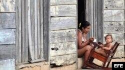 Una madre alimenta a su hija en la puerta de su vivienda en Baracoa. Archivo.