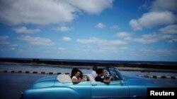 Turistas pasean por el Malecón de La Habana en un auto clásico americano.