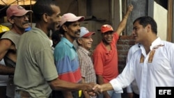 ARCHIVO. El presidente de Ecuador, Rafael Correa saluda a un grupo de obreros en La Habana Vieja (Cuba).