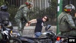 Miembros de la Guardia Nacional Bolivariana detienen a manifestantes.