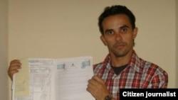 Yoirvis Bravo expone el documento de la propiedad de su vivienda.