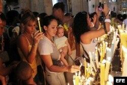 Un grupo de fieles cubanos prende velas dentro de la Iglesia.