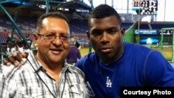 El periodista Edemio Navas (i) junto al jardinero derecho de los Dodgers de Los Ángeles, Yasiel Puig (d).