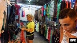Una mujer organiza la mercancía en un pequeño negocio privado de venta de ropa importada en La Habana (Cuba). El Gobierno de Cuba ordenó hoy el cierre de las salas privadas de cine 3D que han proliferado en la isla en el último año, al tiempo que puso un