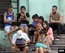 Un grupo de jóvenes se conectan a internet en una zona WiFi, en La Habana.