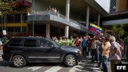 El dirigente opositor venezolano, Carlos Ocariz, permanece dentro de una camioneta mientras personas adeptas al gobierno nacional impiden su paso al Consejo Nacional Electoral (CNE).