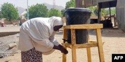 Mujer en Borno, Nigeria, se lava las manos de acuerdo a instrucciones de prevención de COVID-19