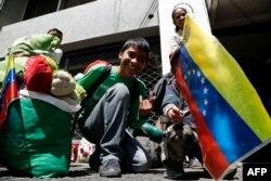 Migrantes venezolanos esperan frente a la embajadade su país en Quito para regresar a Venezuela.
