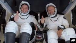Los astronautas Robert Behnken (izq.) y Douglas Hurley saludan a su regreso a la Tierra dentro de la cápsula SpaceX Dragon.