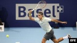 El tenista suizo Roger Federer devuelve la pelota…