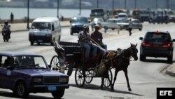 HAB04. LA HABANA (CUBA), 20/08/12 .- Dos hombres transitan en un coche hoy, lunes 20 de agosto de 2012, en La Habana (Cuba). El Estado cubano autorizó la creación de la primera sección sindical de cocheros, conductores de carros tirados por caballos, form