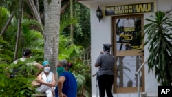 Personas esperan afuera de una oficina de la Western Union en La Habana.