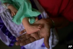 Nelida López sostiene el pie de Peyton, su nieta recién nacida