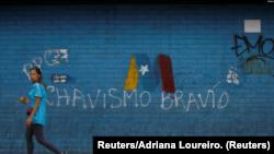 Una mujer pasa frente a un graffiti de la campaña de Nicolás Maduro