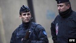 """Agentes de policía franceses permanecen en guardia en una calle junto a la sede del semanario satírico francés """"Charlie Hebdo""""."""